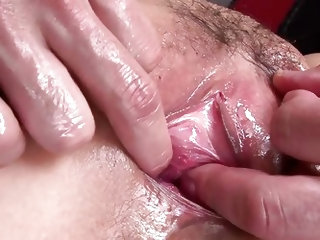 She is glistening, thanks to all the oil that is dripping off her body and she bends over, to get fingered from behind, as her tits are groped. The tw