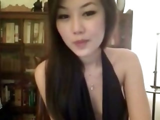 Pretty amateur Asian girl actually has some nice curves and she's not afraid to show them off. She props a pillow under her head and looks down whil