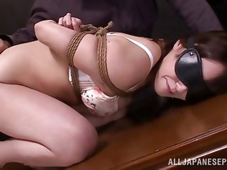 She is tied up by her master with rope and made to look, like a dirty slut by him. Her big natural tits are hanging out and she is collared, and has h