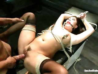 She's a brunette asian bitch that the guy tied on a table and now he's having fun with her! Her big natural breasts with metal clamps on the